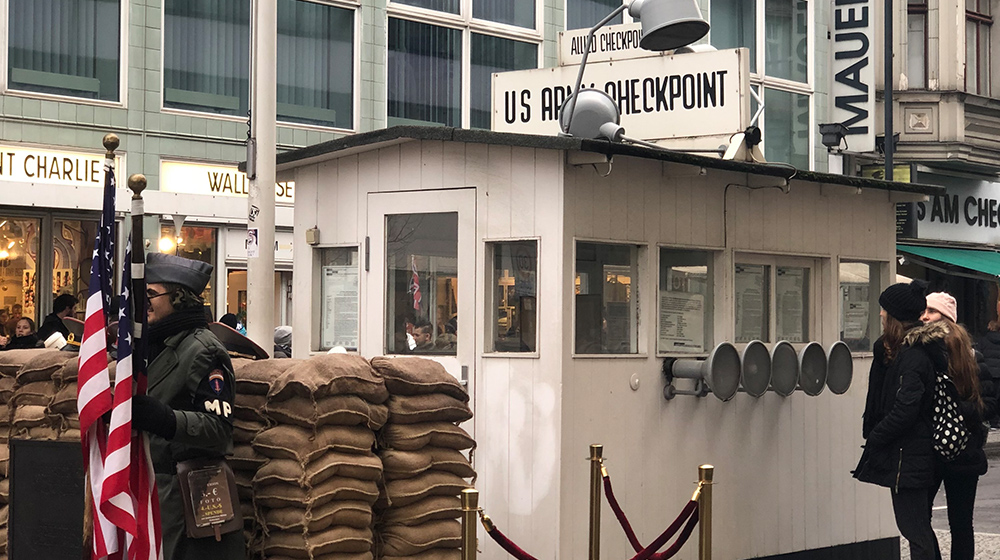 Checkpoint Charlie gatehouse with people dressed as soldiers holding an American flag