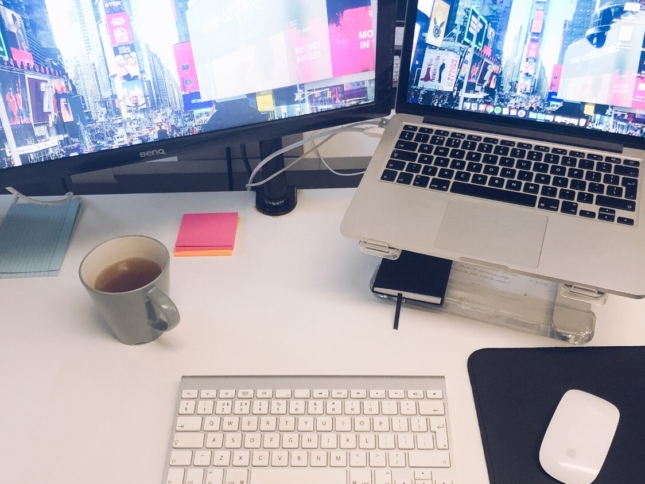 Desk with laptop, screen, mouse, keyboard, and tea.